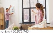 Купить «happy couple moving to new home and hanging photo», видеоролик № 30975743, снято 10 июня 2019 г. (c) Syda Productions / Фотобанк Лори