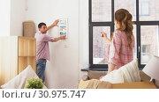 Купить «happy couple moving to new home and hanging photo», видеоролик № 30975747, снято 10 июня 2019 г. (c) Syda Productions / Фотобанк Лори