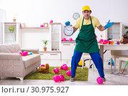Купить «Young male contractor doing housework after party», фото № 30975927, снято 14 марта 2019 г. (c) Elnur / Фотобанк Лори