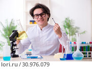 Купить «Young male biochemist working in the lab», фото № 30976079, снято 14 января 2019 г. (c) Elnur / Фотобанк Лори