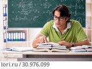 Купить «Handsome student in front of chalkboard with formulas», фото № 30976099, снято 6 ноября 2018 г. (c) Elnur / Фотобанк Лори