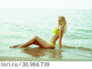 Beautiful young girl with a slim perfect sexy body sits in the water on a sandy beach by the sea. Стоковое фото, фотограф katalinks / Фотобанк Лори