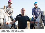 Купить «Positive mature couple with jockey learn to riding horse at farm», фото № 30985203, снято 12 декабря 2019 г. (c) Яков Филимонов / Фотобанк Лори