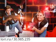 Купить «satisfied teen boy having fun on laser tag arena with his older», фото № 30985235, снято 3 сентября 2018 г. (c) Яков Филимонов / Фотобанк Лори