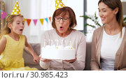 Купить «mother, daughter, grandmother with birthday cake», видеоролик № 30985423, снято 14 июня 2019 г. (c) Syda Productions / Фотобанк Лори