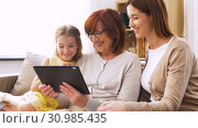 Купить «mother, daughter and grandmother with tablet pc», видеоролик № 30985435, снято 14 июня 2019 г. (c) Syda Productions / Фотобанк Лори