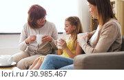 Купить «mother, daughter and grandmother having tea party», видеоролик № 30985467, снято 14 июня 2019 г. (c) Syda Productions / Фотобанк Лори