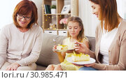 Купить «mother, daughter and grandmother eating cake», видеоролик № 30985471, снято 14 июня 2019 г. (c) Syda Productions / Фотобанк Лори