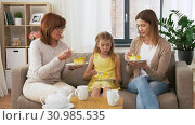 Купить «mother, daughter and grandmother eating cake», видеоролик № 30985535, снято 14 июня 2019 г. (c) Syda Productions / Фотобанк Лори