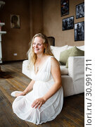 Купить «Portrait of a beautiful long-haired pregnant blonde, gracefully sitting on floor», фото № 30991711, снято 15 декабря 2019 г. (c) Ирина Мойсеева / Фотобанк Лори