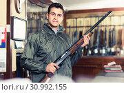 Купить «Confident hunter male wearing windbreaker in hunting shop with rifle in hands», фото № 30992155, снято 11 декабря 2017 г. (c) Яков Филимонов / Фотобанк Лори