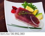 Купить «Delicious raw tuna fish served with fresh avocado and greens», фото № 30992383, снято 26 июня 2019 г. (c) Яков Филимонов / Фотобанк Лори