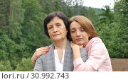 Portrait of a serious mother and adult daughter against the backdrop of the mountains in the summer. Happy old age, mother's day, daughter travels with an elderly mother. Стоковое видео, видеограф Ольга Балынская / Фотобанк Лори