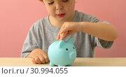 Купить «Little boy putting coins in a piggy bank», фото № 30994055, снято 4 апреля 2020 г. (c) Ekaterina Demidova / Фотобанк Лори