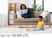 Купить «mother with laptop looking at baby with toy blocks», фото № 30994275, снято 22 марта 2019 г. (c) Syda Productions / Фотобанк Лори