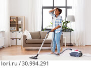 Купить «tired african woman with vacuum cleaner at home», фото № 30994291, снято 7 апреля 2019 г. (c) Syda Productions / Фотобанк Лори