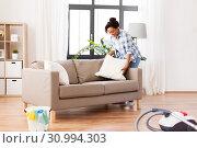 Купить «african american woman arranging sofa cushions», фото № 30994303, снято 7 апреля 2019 г. (c) Syda Productions / Фотобанк Лори