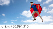 Купить «man in red superhero cape flying over sky», фото № 30994315, снято 3 февраля 2019 г. (c) Syda Productions / Фотобанк Лори