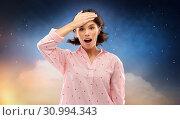 Купить «confused young woman in pajama over night sky», фото № 30994343, снято 6 марта 2019 г. (c) Syda Productions / Фотобанк Лори