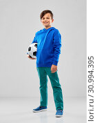 Купить «smiling boy in blue hoodie with soccer ball», фото № 30994395, снято 9 марта 2019 г. (c) Syda Productions / Фотобанк Лори