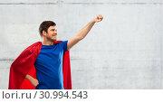 Купить «man in red superhero cape over concrete background», фото № 30994543, снято 3 февраля 2019 г. (c) Syda Productions / Фотобанк Лори
