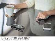 woman with coffee using black interactive panel. Стоковое фото, фотограф Syda Productions / Фотобанк Лори