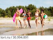 Купить «friends run with beach ball and swimming mattress», фото № 30994891, снято 29 июля 2018 г. (c) Syda Productions / Фотобанк Лори