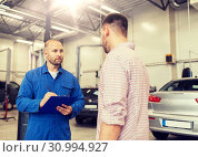 Купить «auto mechanic with clipboard and man at car shop», фото № 30994927, снято 1 июля 2016 г. (c) Syda Productions / Фотобанк Лори