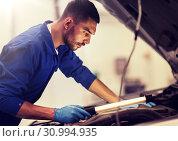 Купить «mechanic man with lamp repairing car at workshop», фото № 30994935, снято 1 июля 2016 г. (c) Syda Productions / Фотобанк Лори