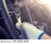 Купить «mechanic man with wrench repairing car at workshop», фото № 30994943, снято 1 июля 2016 г. (c) Syda Productions / Фотобанк Лори