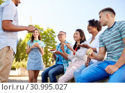 Купить «friends eating sandwiches or burgers in park», фото № 30995027, снято 10 июня 2018 г. (c) Syda Productions / Фотобанк Лори