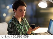 Купить «businesswoman using smart speaker at night office», фото № 30995059, снято 23 февраля 2019 г. (c) Syda Productions / Фотобанк Лори