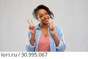 Купить «happy african american woman showing peace», фото № 30995067, снято 2 марта 2019 г. (c) Syda Productions / Фотобанк Лори