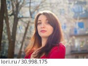 Young brunette woman with sensual lips in red shirt enjoying spring breeze outdoors while the sun is shining. Стоковое фото, фотограф Ольга Балынская / Фотобанк Лори