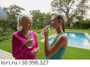 Female trainer and active senior woman drinking water in the backyard. Стоковое фото, агентство Wavebreak Media / Фотобанк Лори