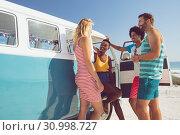 Купить «Group of friends talking with each other near camper van at beach in the sunshine», фото № 30998727, снято 15 марта 2019 г. (c) Wavebreak Media / Фотобанк Лори