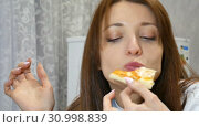 Beautiful young girl is biting slice of pizza with mushrooms, cheese, maize, olives, red onion rings and tomatoes sitting at home. Стоковое видео, видеограф Ольга Балынская / Фотобанк Лори