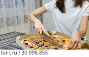 Portrait of female hands cuting a hot pizza with mushrooms, cheese, maize, olives, red onion rings and tomatoes in a cardboard box using knife. Стоковое видео, видеограф Ольга Балынская / Фотобанк Лори