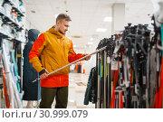 Man choosing ski poles, shopping in sports shop. Стоковое фото, фотограф Tryapitsyn Sergiy / Фотобанк Лори