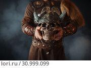 Купить «Viking holds human skull in helmet», фото № 30999099, снято 27 марта 2019 г. (c) Tryapitsyn Sergiy / Фотобанк Лори