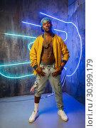 Купить «Black rapper in underpass neon light on background», фото № 30999179, снято 5 апреля 2019 г. (c) Tryapitsyn Sergiy / Фотобанк Лори