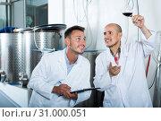 Купить «Two smiling workers standing with glass of wine», фото № 31000051, снято 15 сентября 2019 г. (c) Яков Филимонов / Фотобанк Лори