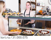 Купить «Bakery female worker with delicious pies and rolls on counter», фото № 31000075, снято 22 апреля 2017 г. (c) Яков Филимонов / Фотобанк Лори