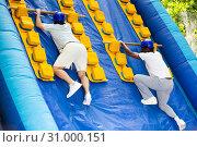 Купить «Mens competition on an inflatable slide Great race in an amusement park», фото № 31000151, снято 29 мая 2019 г. (c) Яков Филимонов / Фотобанк Лори