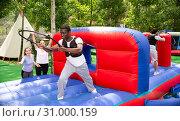 Купить «Competition of two men - who quickly throw a hoop on a stick», фото № 31000159, снято 29 мая 2019 г. (c) Яков Филимонов / Фотобанк Лори