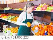 Купить «Nice female in apron selling fresh oranges», фото № 31000223, снято 24 июня 2019 г. (c) Яков Филимонов / Фотобанк Лори