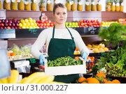 Купить «Salesgirl offering green beans», фото № 31000227, снято 31 января 2019 г. (c) Яков Филимонов / Фотобанк Лори