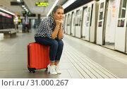 Купить «Woman sitting on suitcase at metro station», фото № 31000267, снято 27 апреля 2018 г. (c) Яков Филимонов / Фотобанк Лори