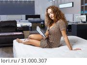 Купить «woman reading brochure while choosing new mattress», фото № 31000307, снято 22 октября 2018 г. (c) Яков Филимонов / Фотобанк Лори
