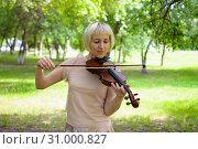 Купить «The Russian woman plays a violin in the park in the summer», фото № 31000827, снято 12 июня 2019 г. (c) Землянникова Вероника / Фотобанк Лори